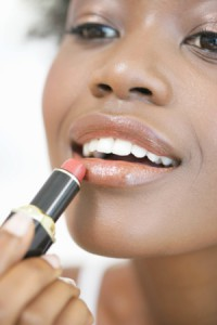 Young woman appying lipstick, smiling, close-up